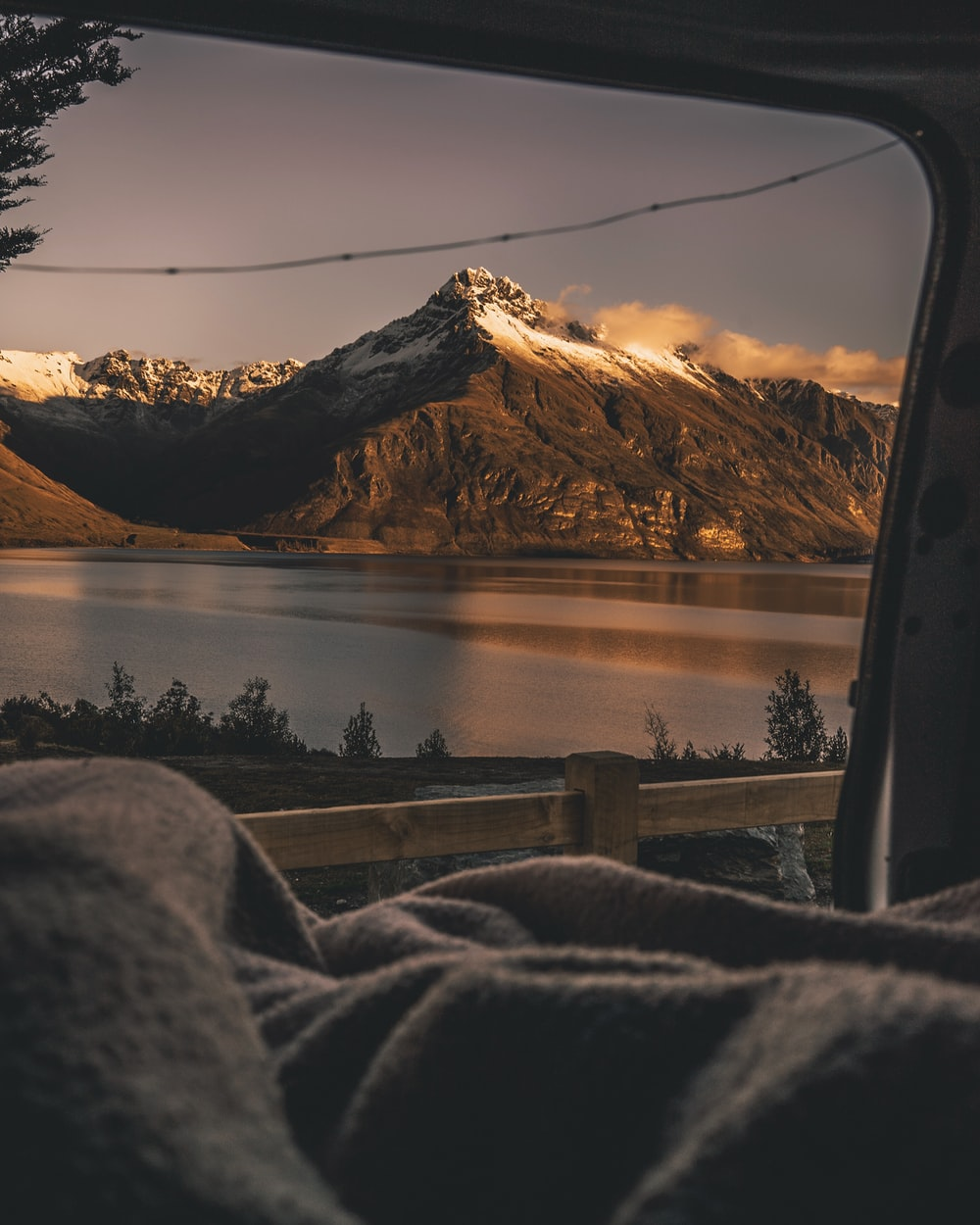 snow capped mountain beside lake view from vehicle door