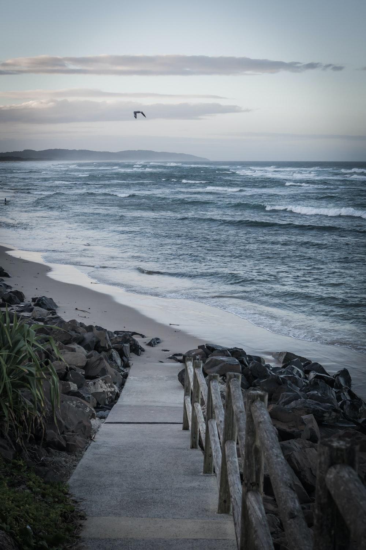 stair on seashore near mountain range