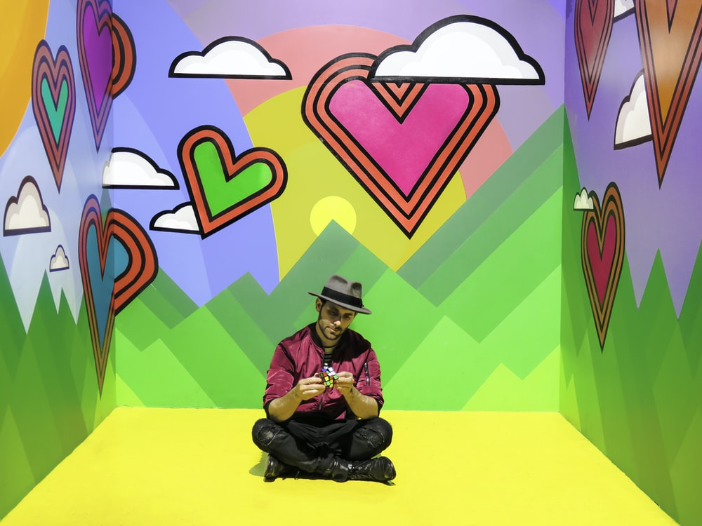 man sitting on multicolored 3D wallpaper room