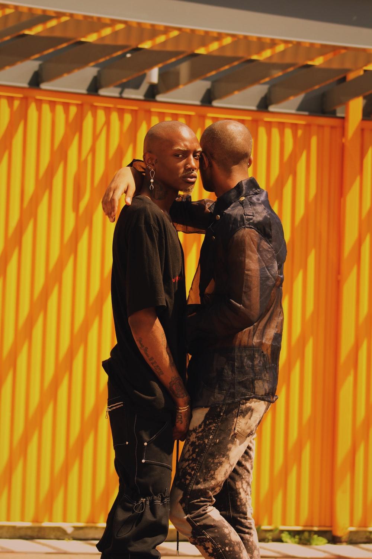 man resting arm on other man's shoulder