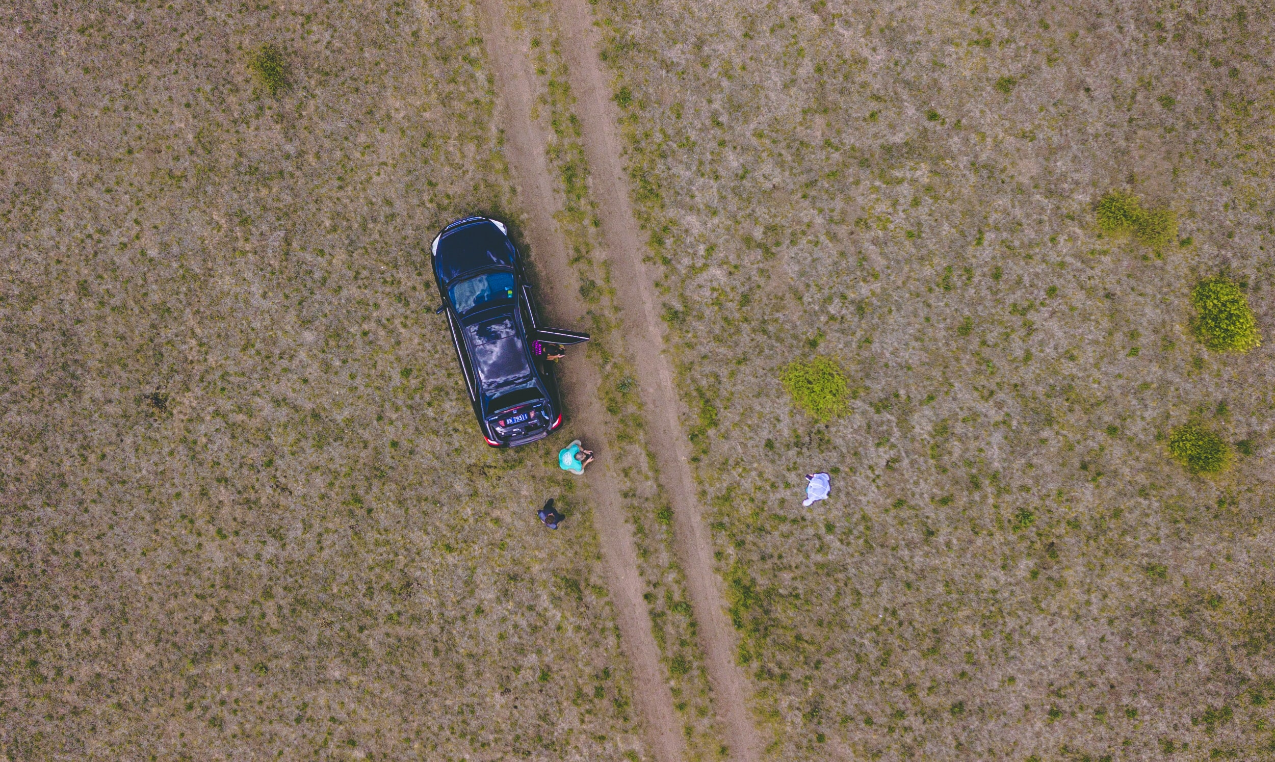 aerial photography of people near black car