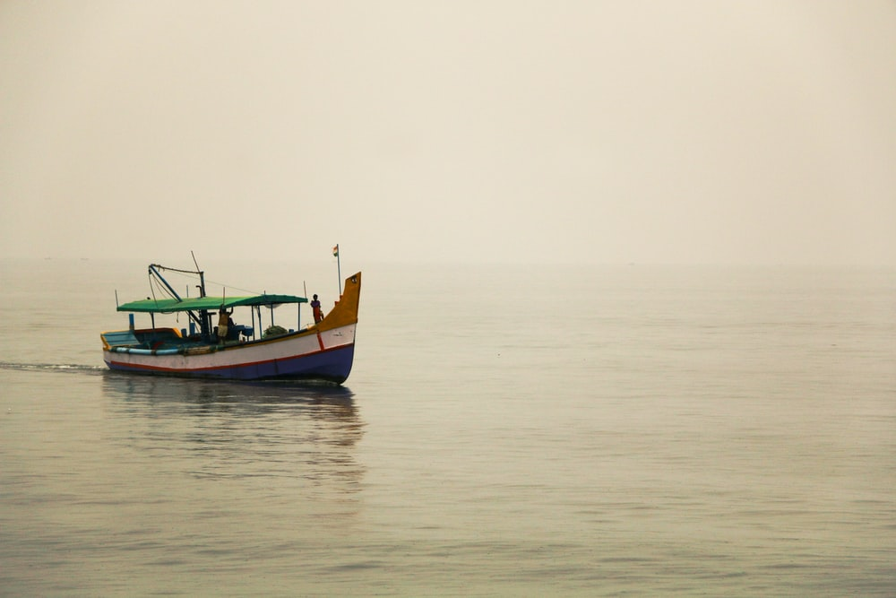 white, blue, and green boat on sea during daytime