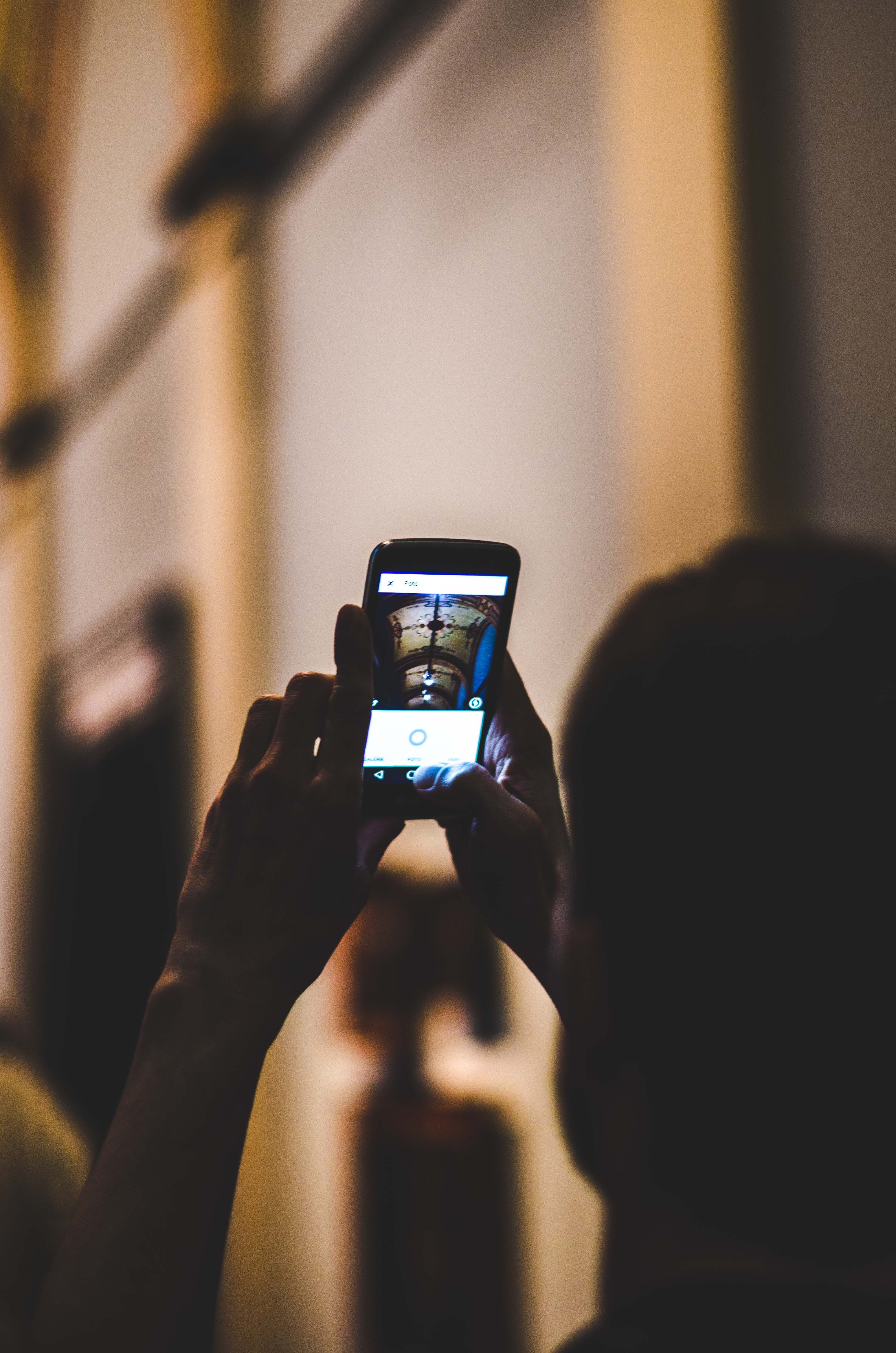selective focus photo of person taking photo on phone
