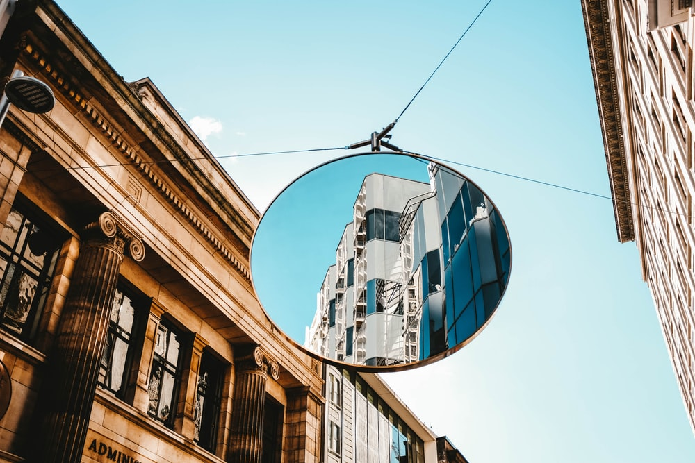 round gray framed mirror in middle of buildings