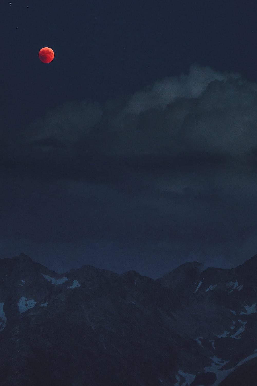 mountain under cloudy full moon