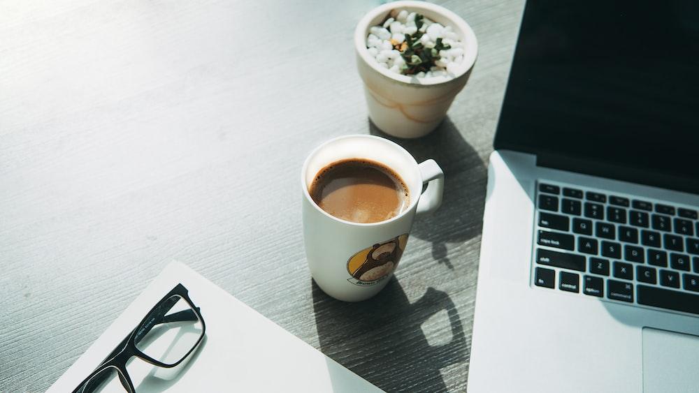 white ceramic mug beside eyeglasses