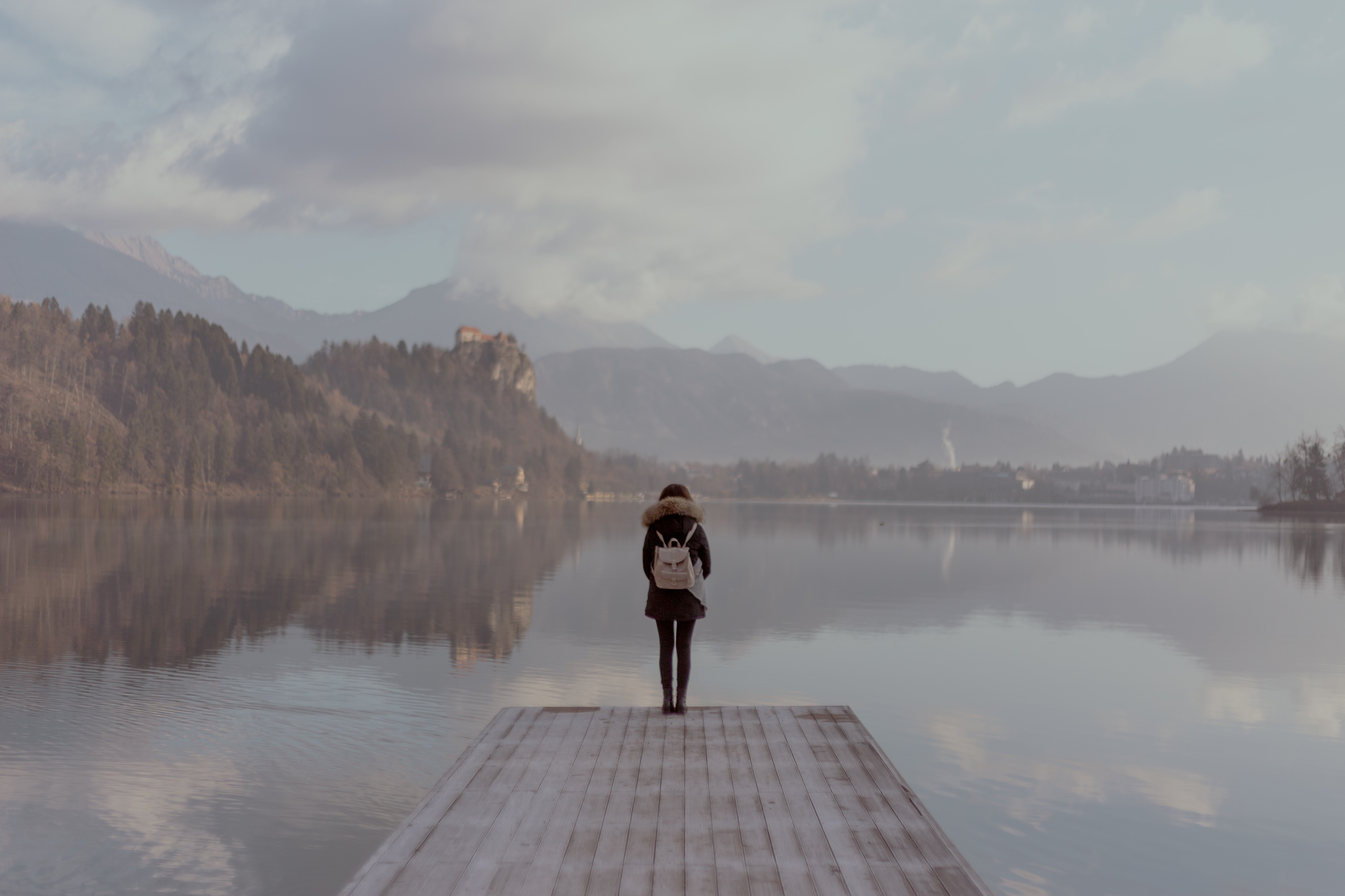 woman standing beside body of calm water