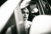 grayscale photography of woman sitting inside car