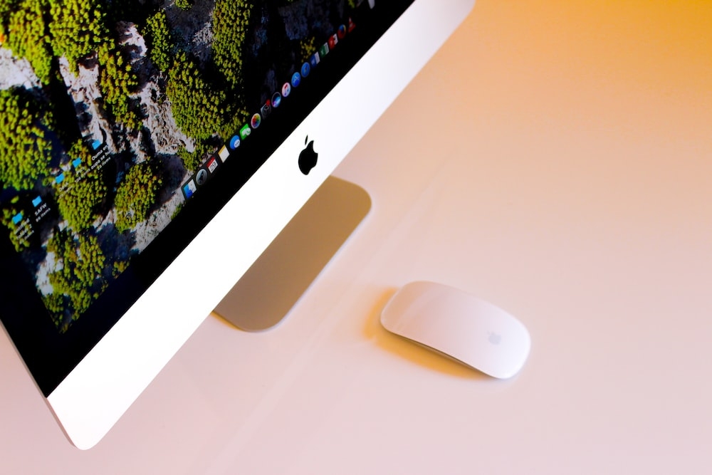 turned-on silver iMac beside Apple Magic Mouse