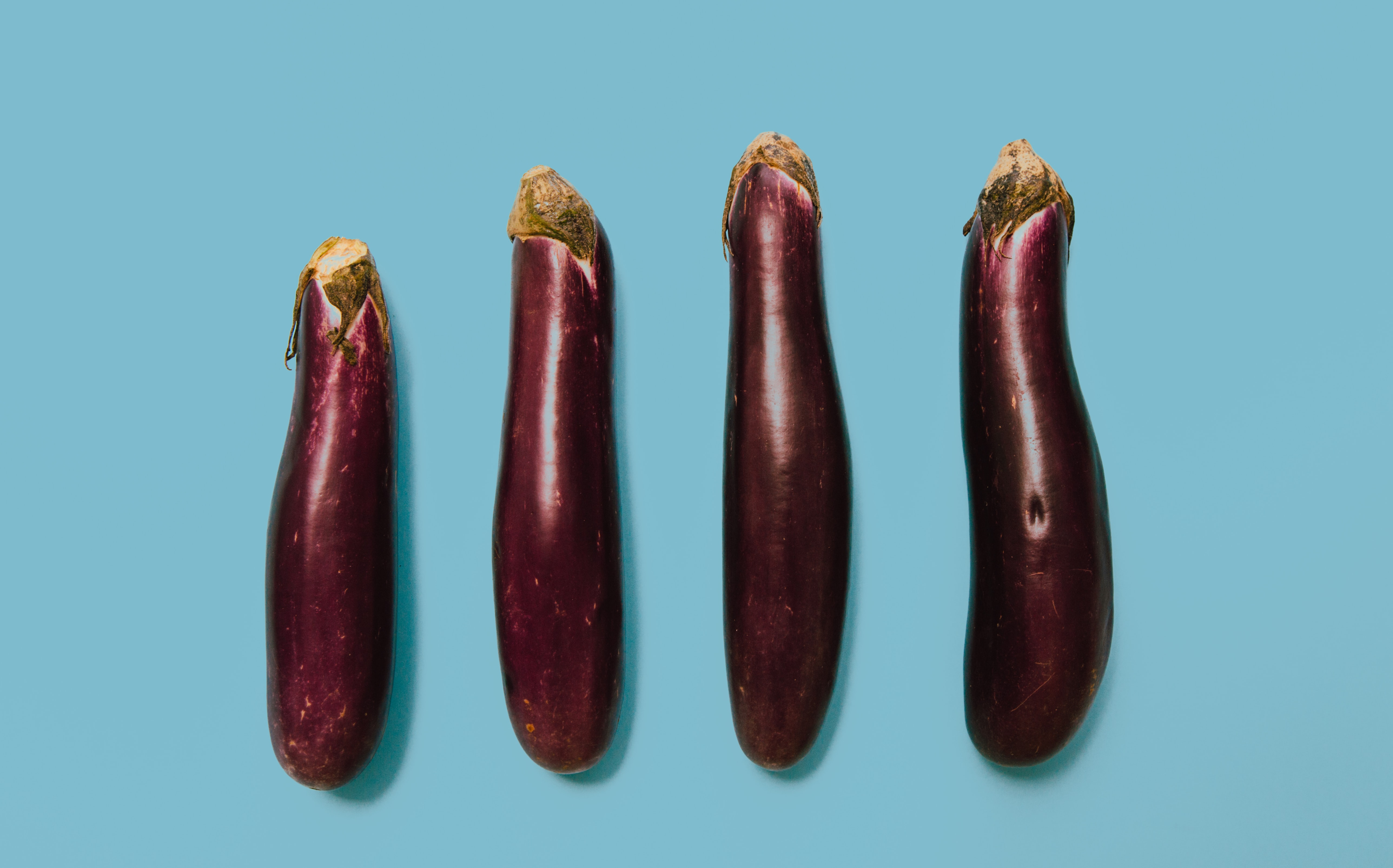 flat lay photography of four purple eggplants