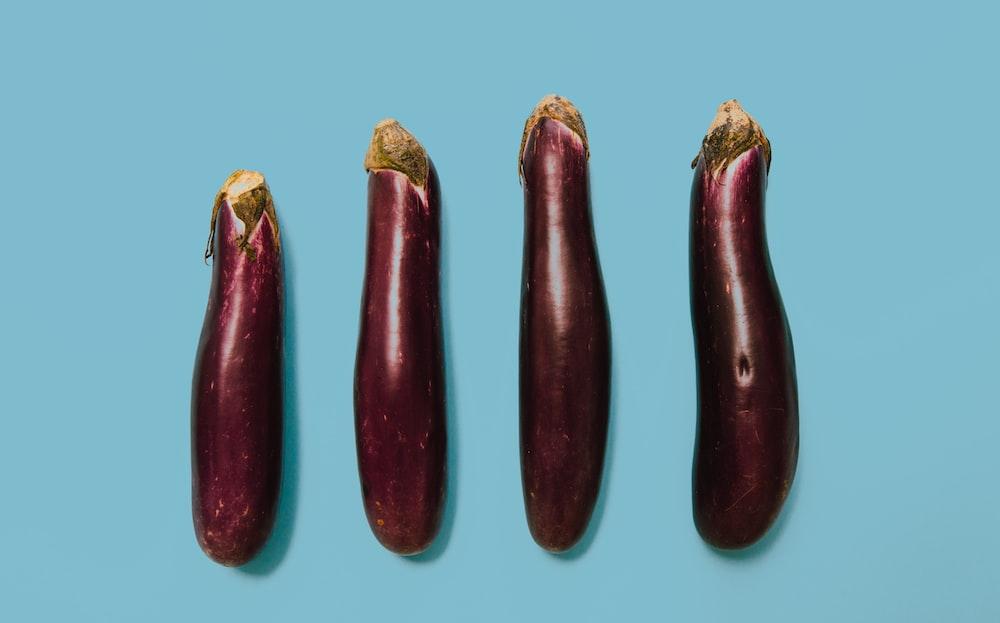 flat lay photography of four purple eggplants