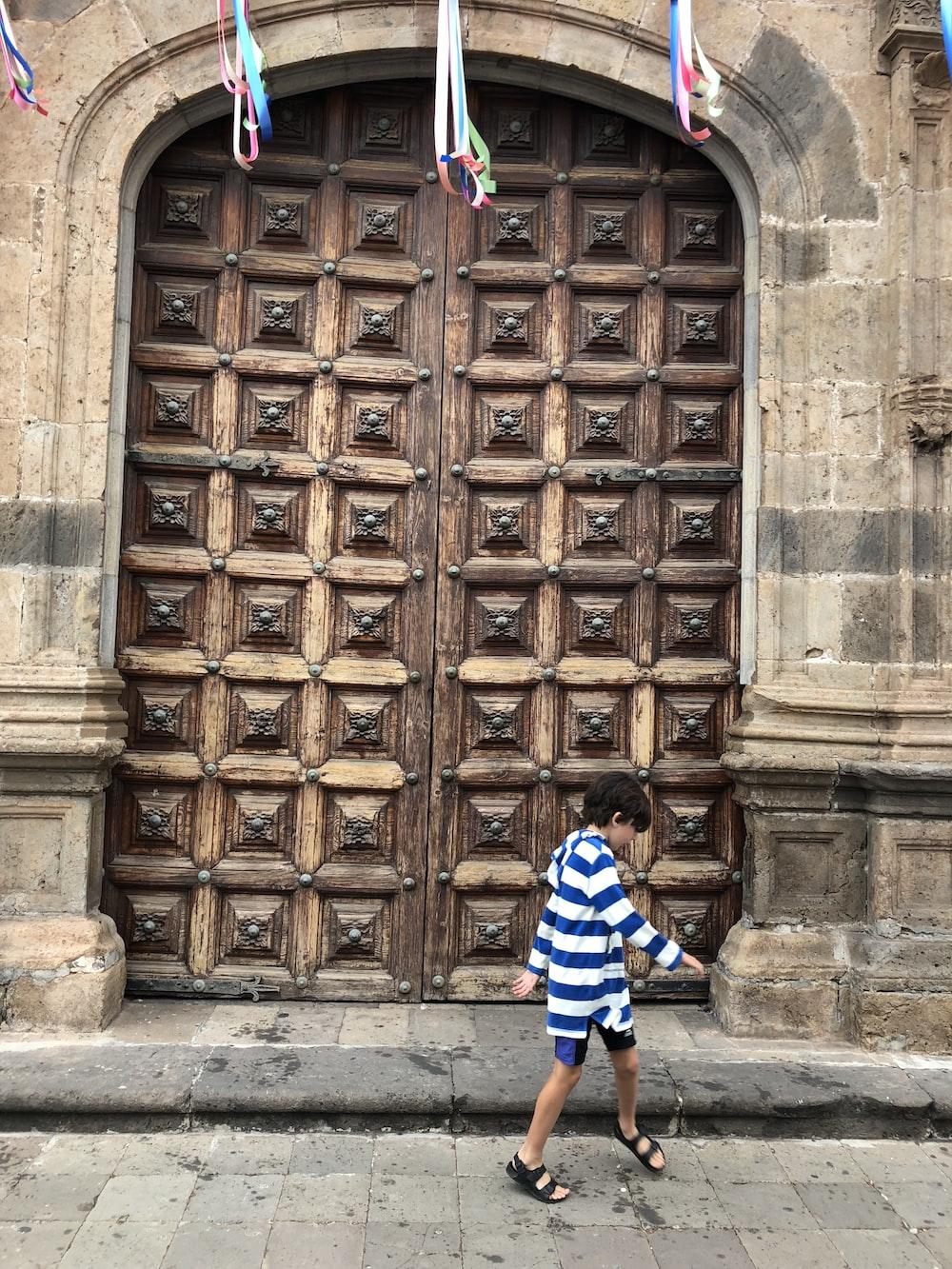 boy walking in front of brown wooden door
