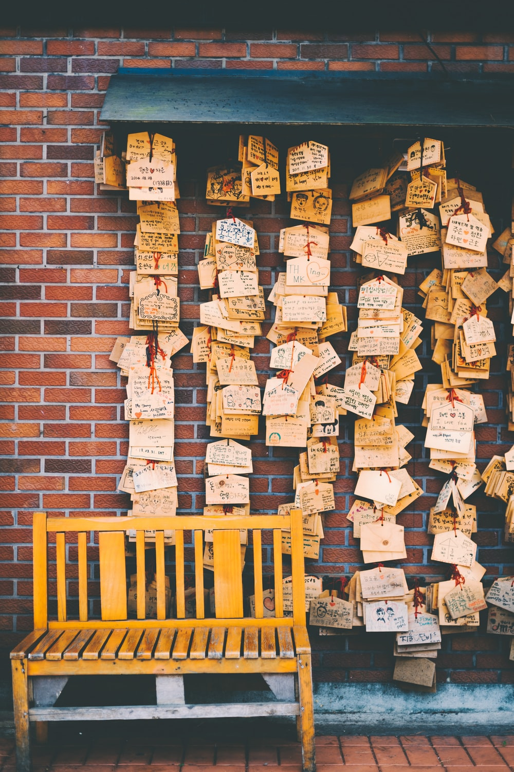brown wooden bench in front of hanging cards