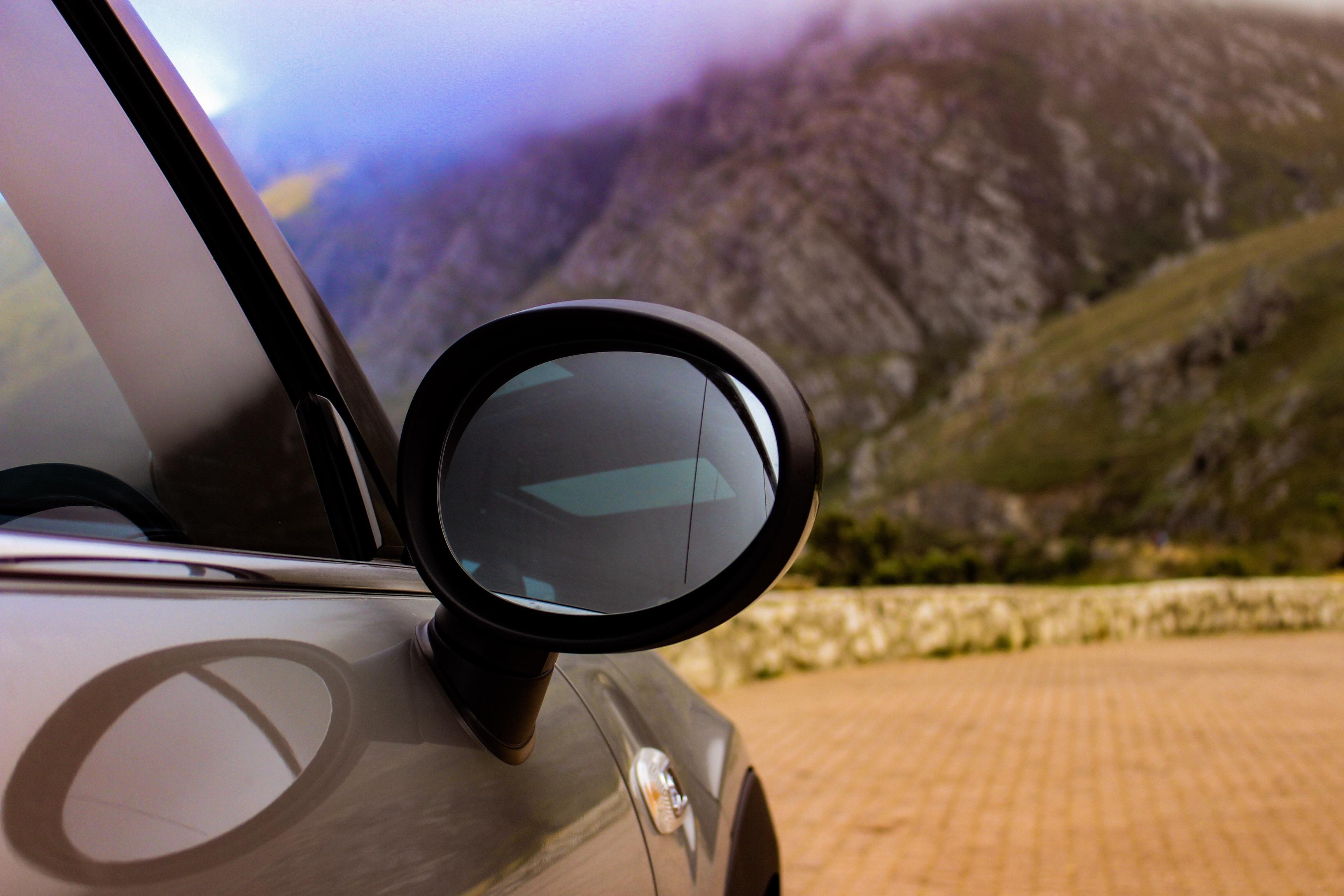 selective focus photography of silver car towards mountain