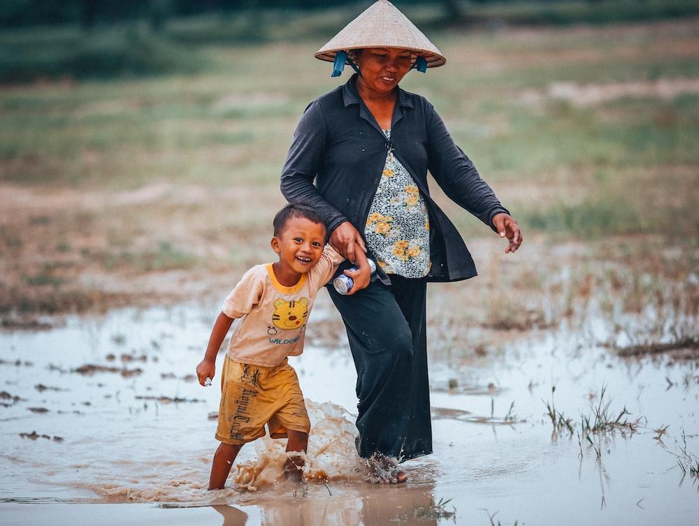 woman and boy walking on rice paddy