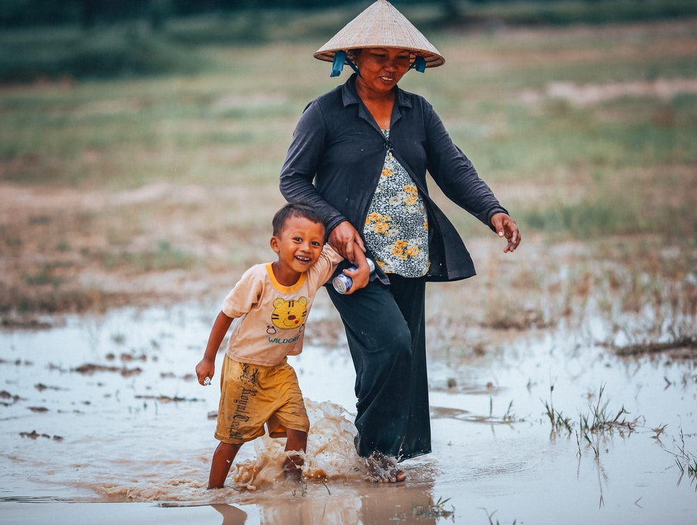 woman and boy walking on rice paddy