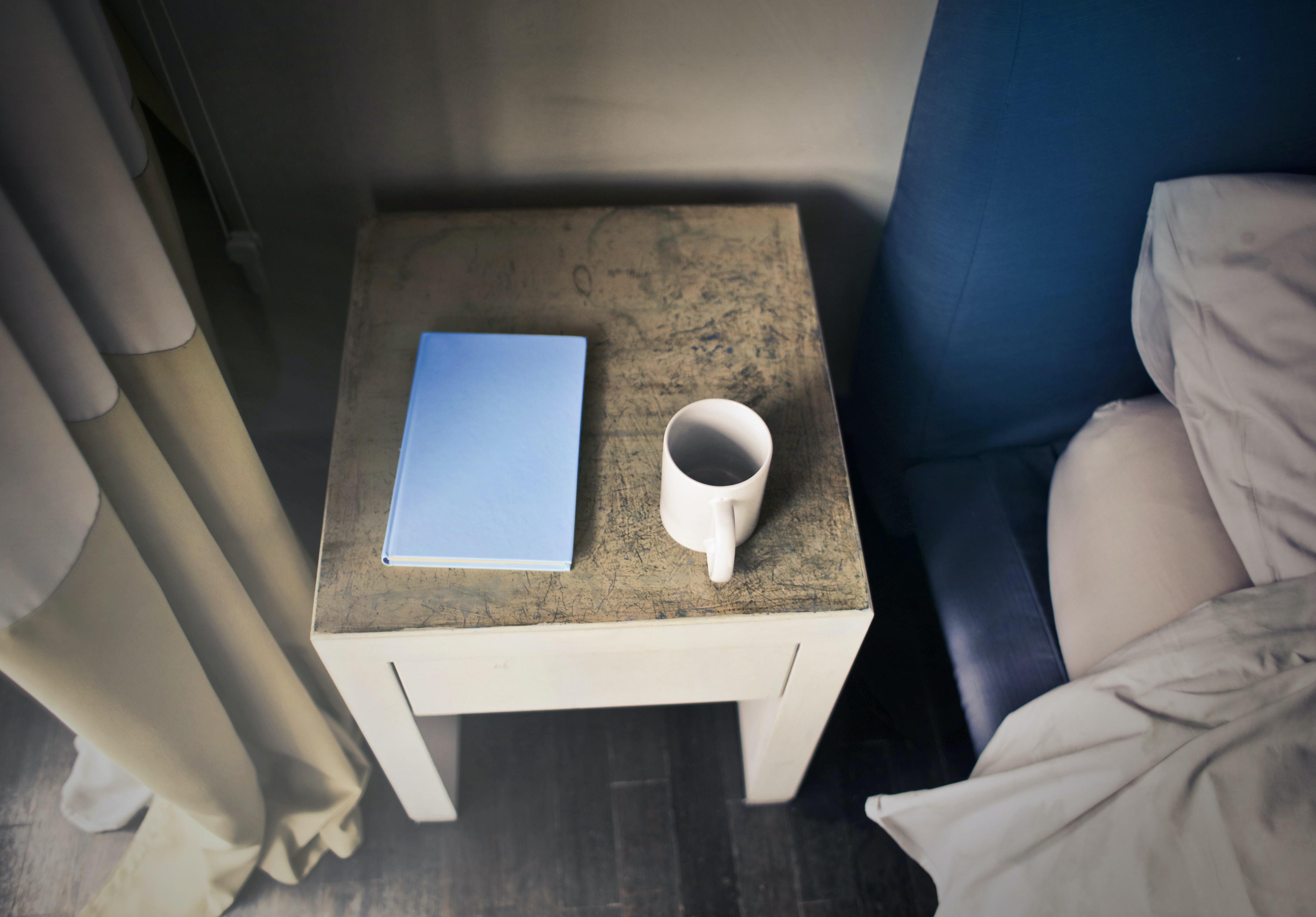 white ceramic mug beside book on wooden table