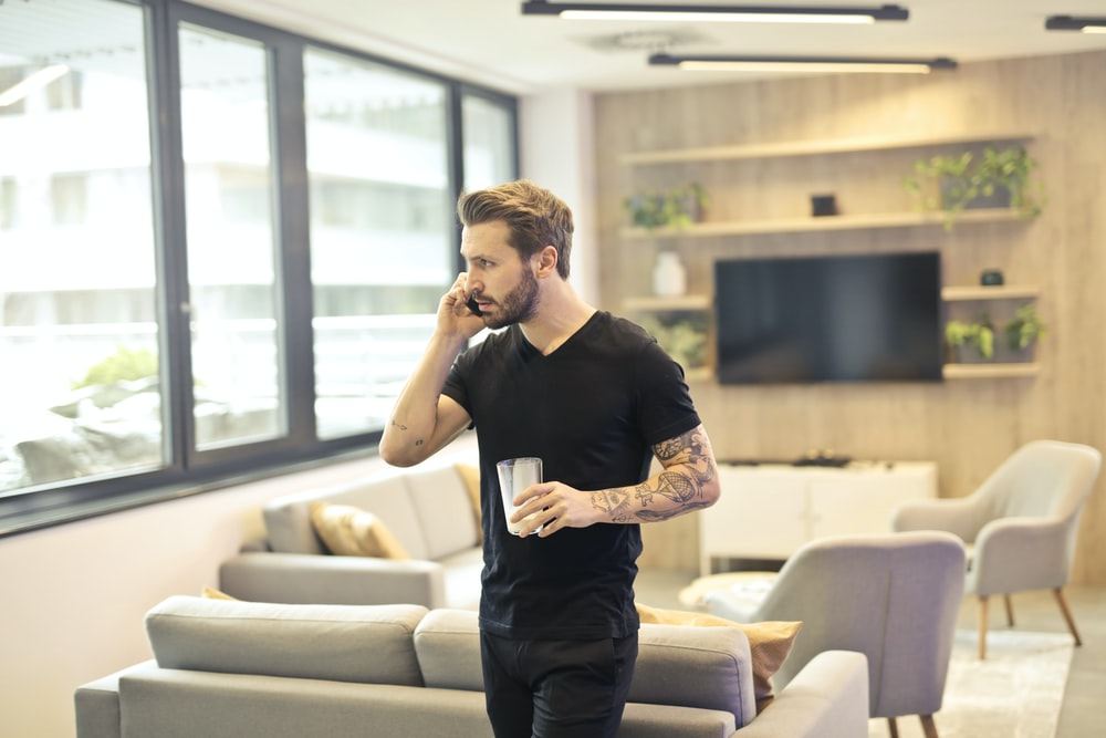 man holding drinking glass while taking a call on phone