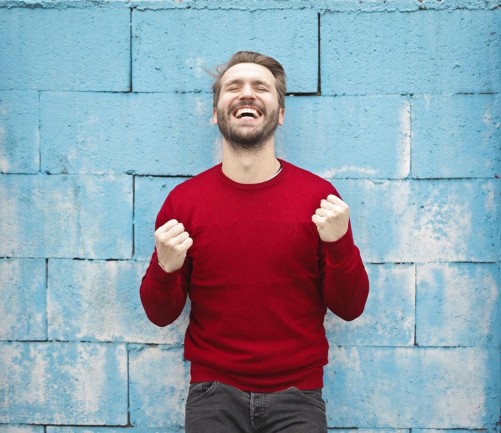 man wearing red long-sleeved shirt standing beside wall