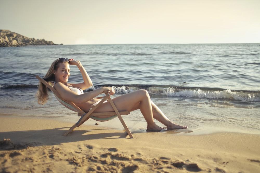 woman sitting on chair near seashore