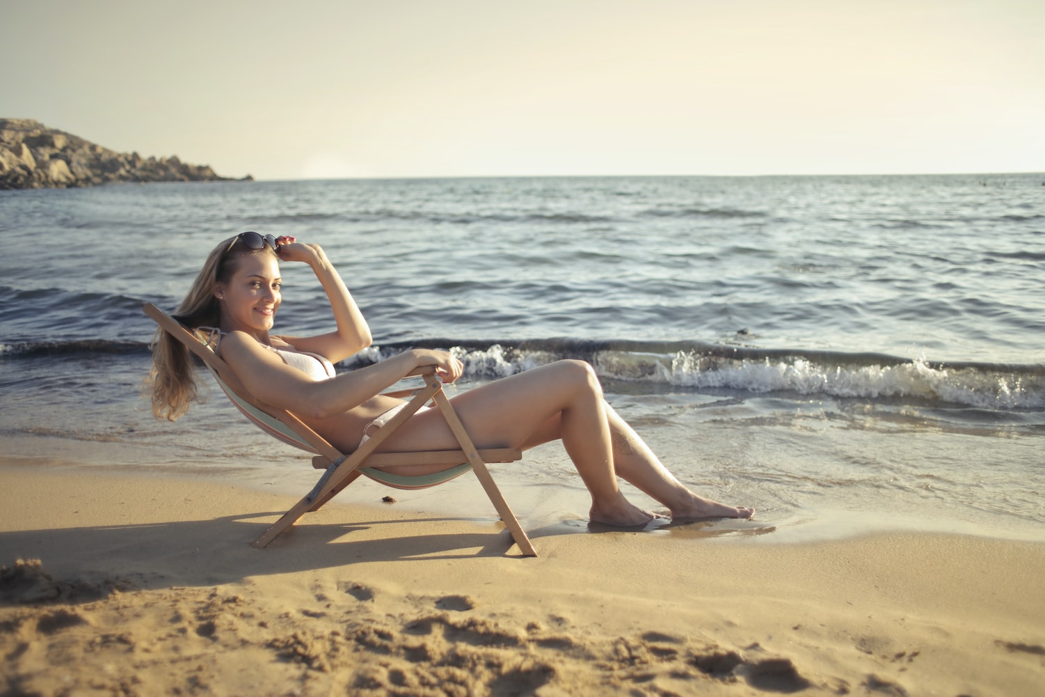 woman sitting on the chair along the  seashore