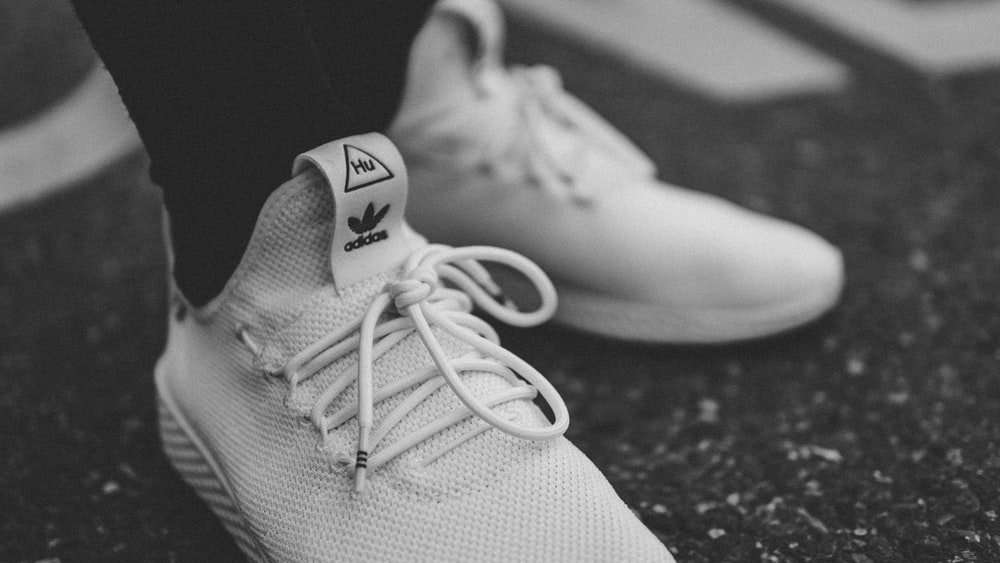 grayscale photo of person in white adidas low-top sneakers