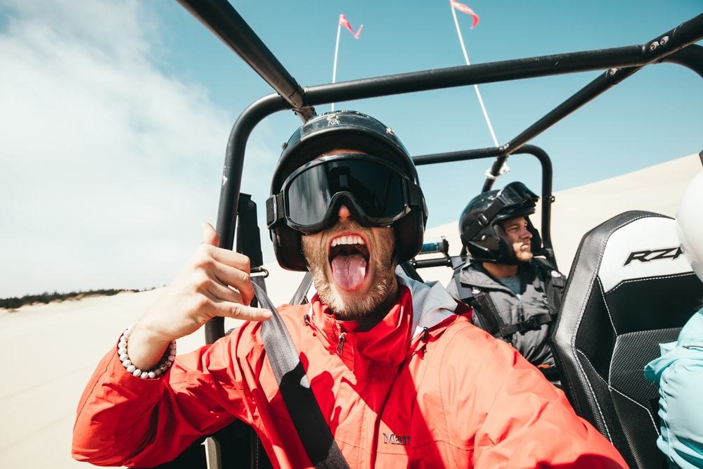 man showing his tongue while riding on ATV