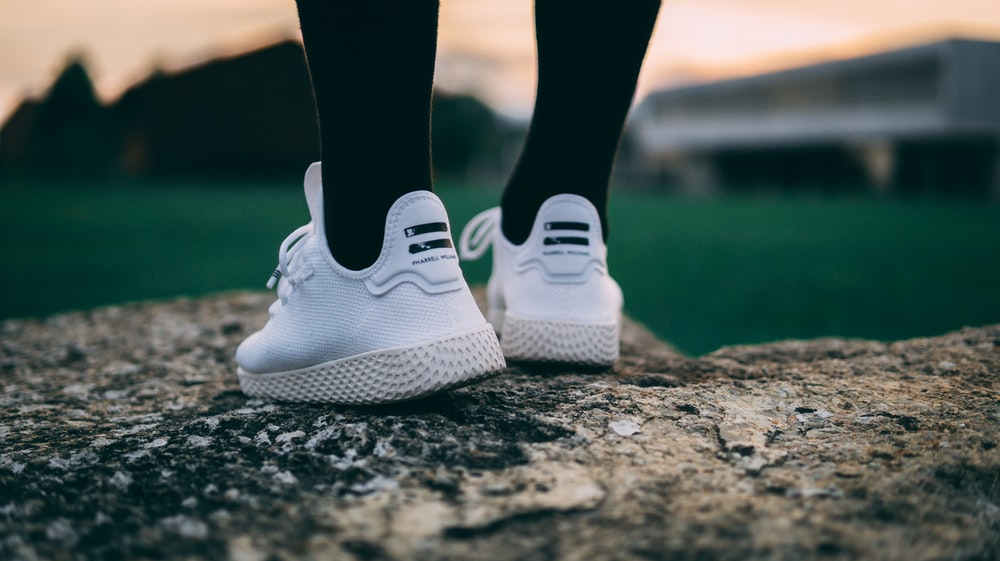 selective focus photography of person wearing shoes standing on rock