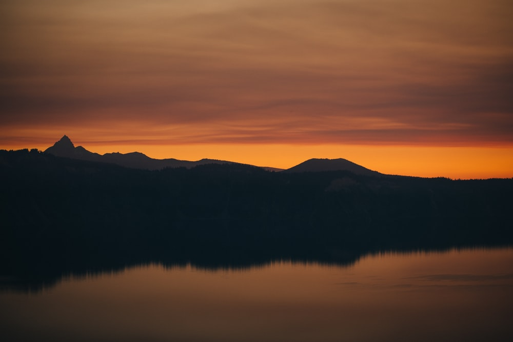 silhouette of mountains near body of water