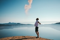 man standing on sand while spreading arms beside calm body of water