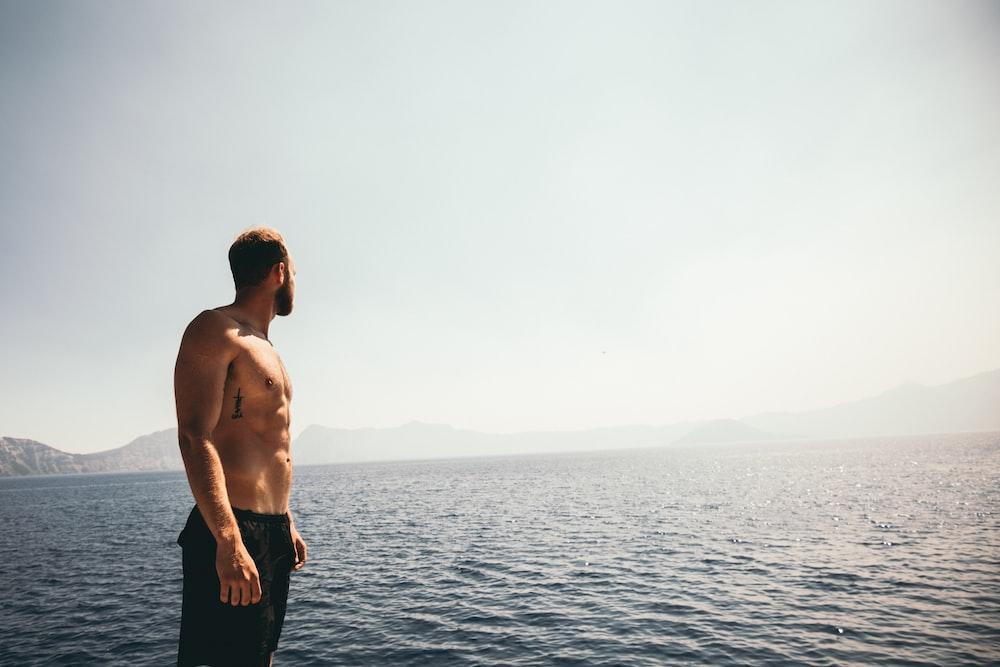 man wearing black shorts standing near ocean