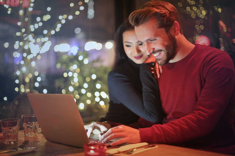 man and woman looking on silver laptop while smiling