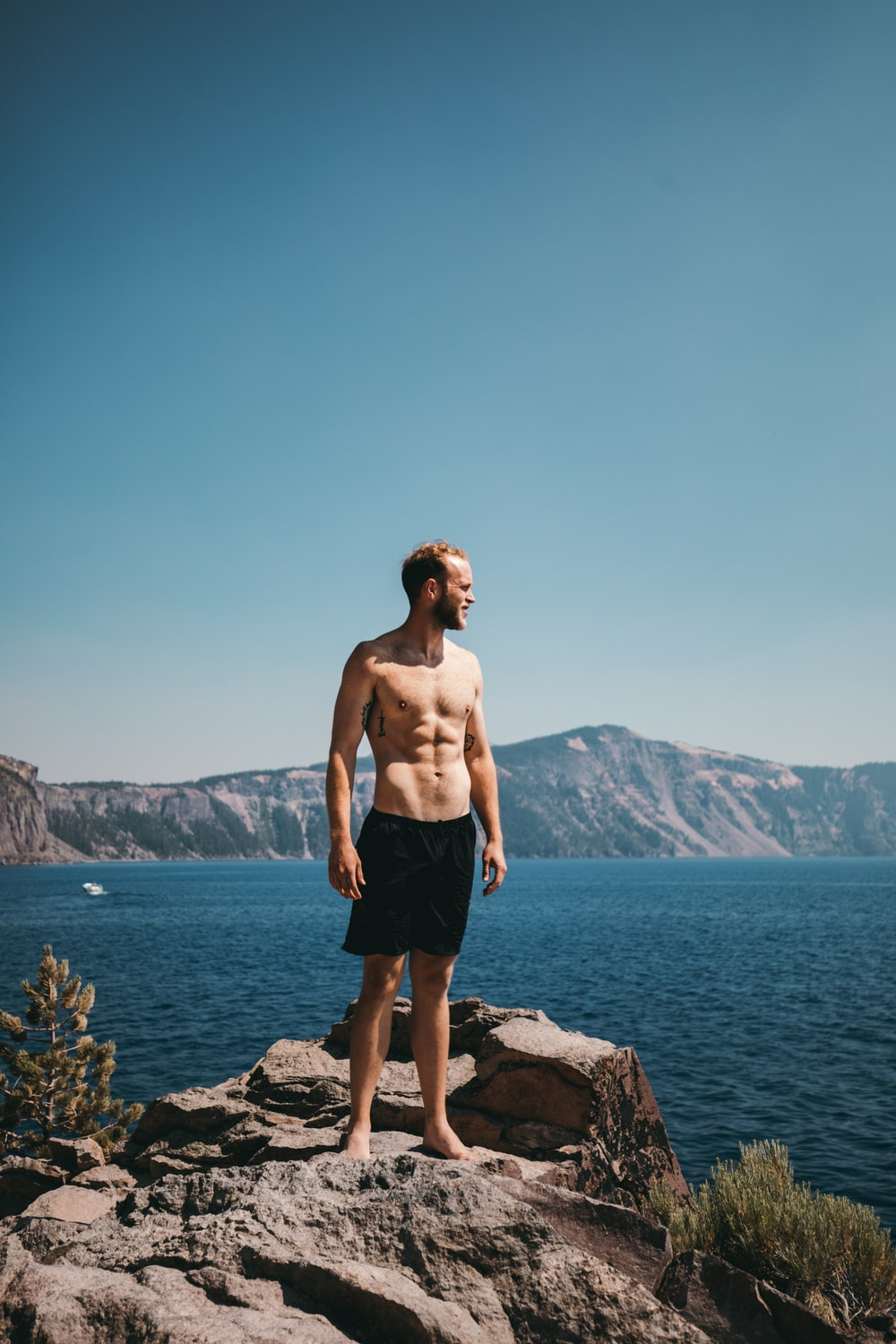man standing on stone formation beside body of water