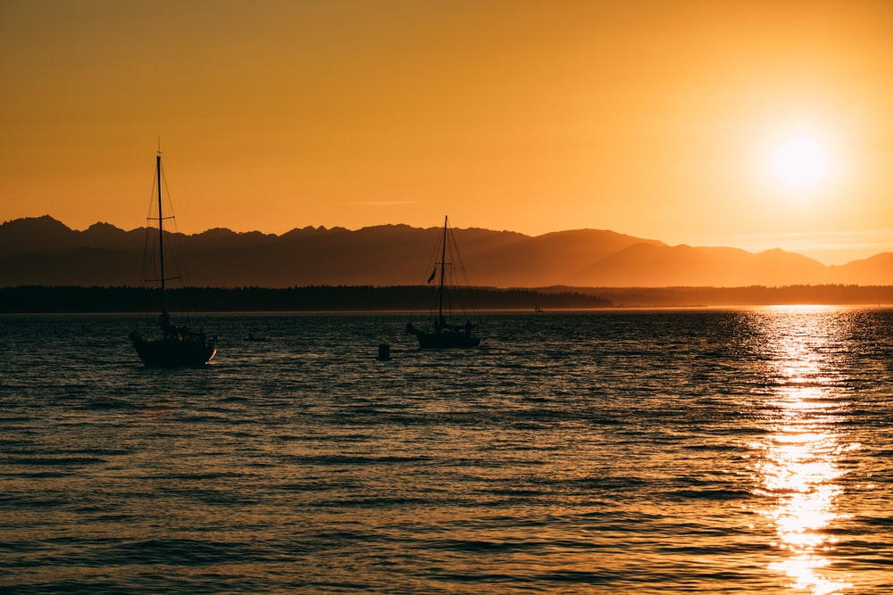 fishing boats on the sea during sunset