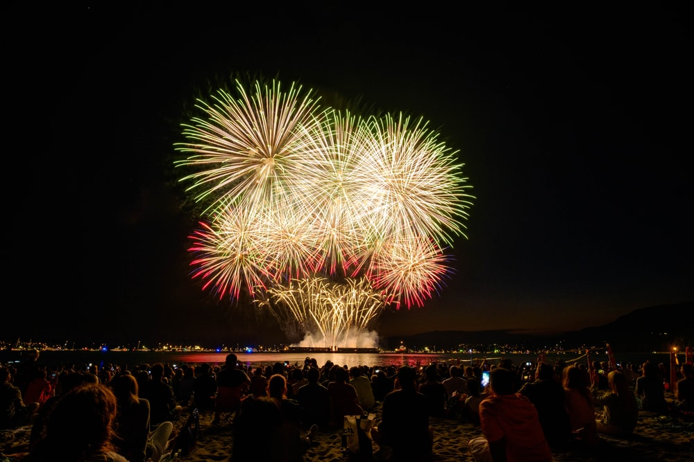 people watching fireworks display during nighttime