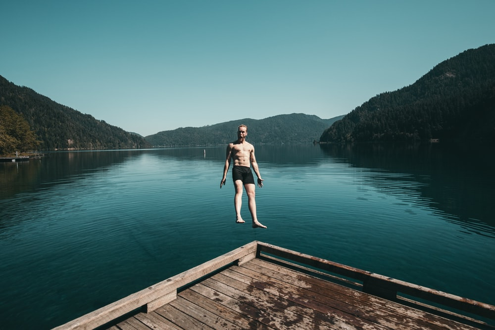 man jumping from brown wooden platform unto lake facing backwards