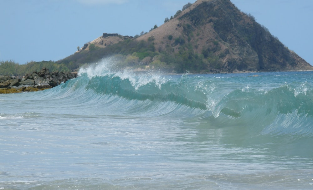 sea wave near mountain at daytime