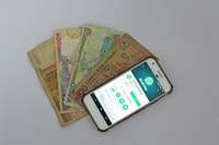 white Android smartphone beside banknotes