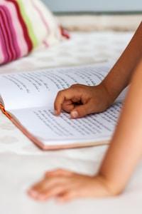 kid's hand pointing on Devanagari script book