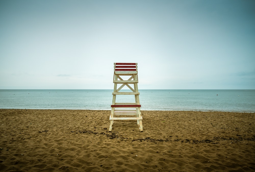 beige wooden lifeguard seat on shore