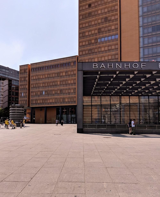 people walking near Bahnhof building