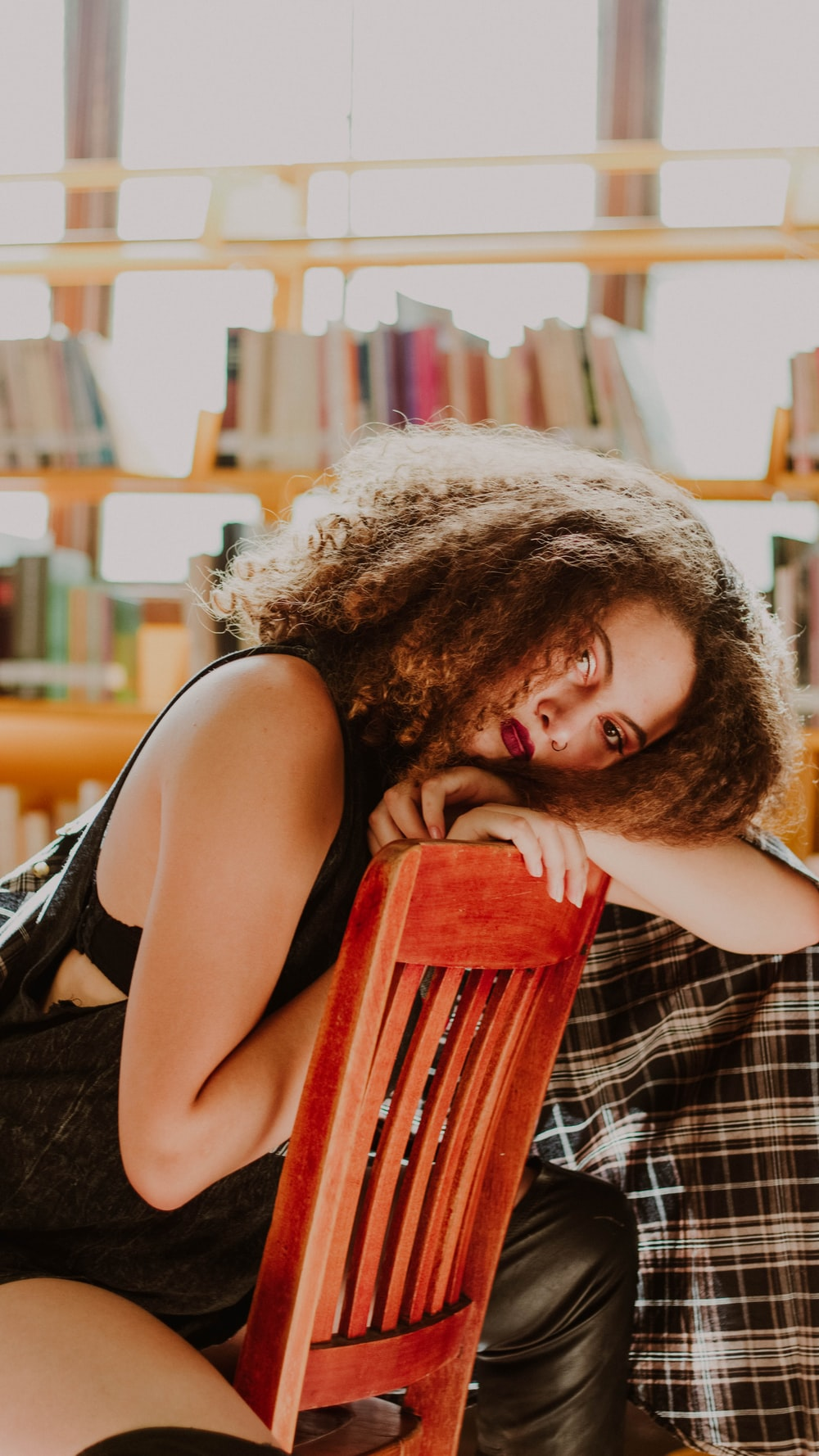 selective focus photography of woman sitting on chair while resting head on backrest