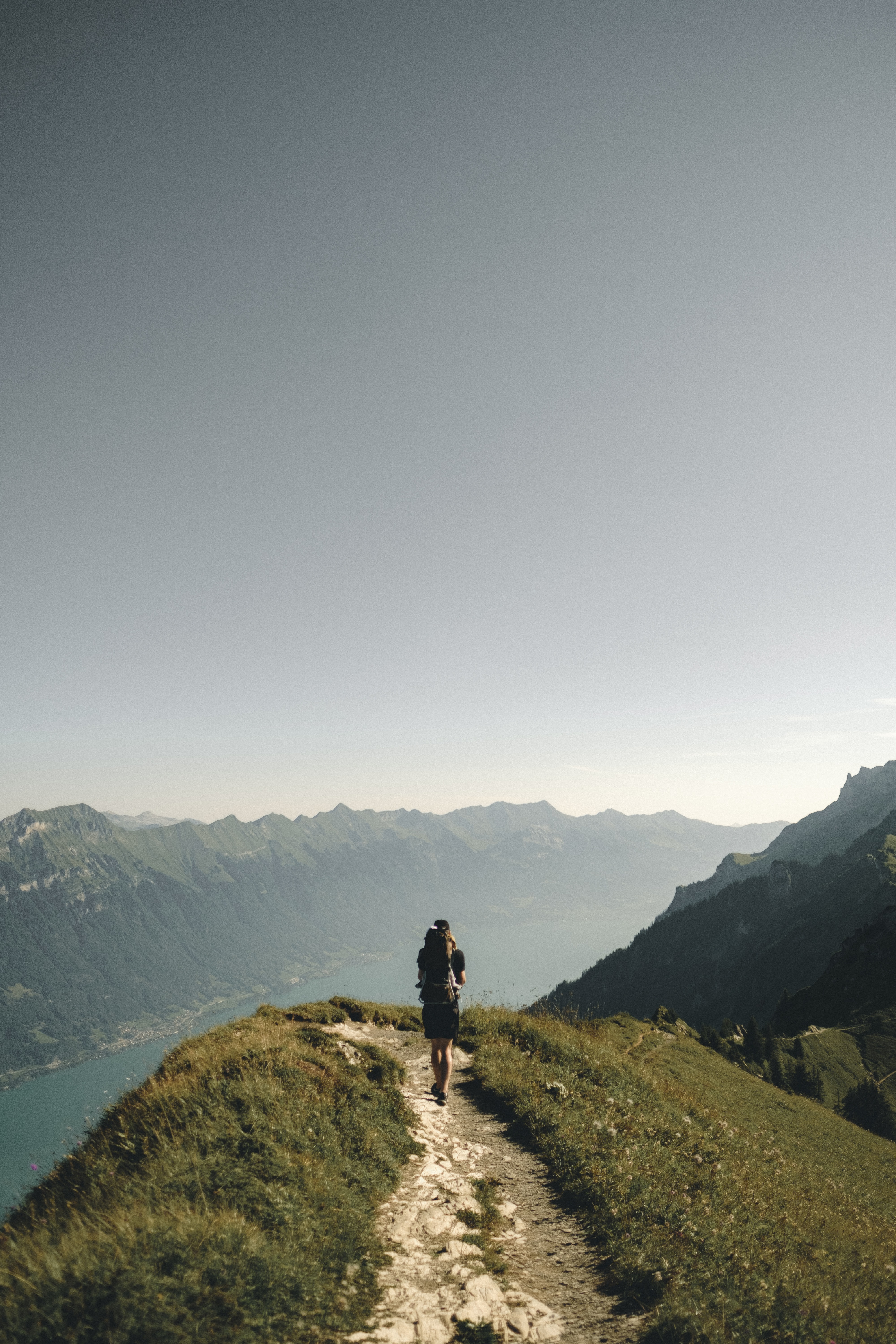 person hiking above mountain overlooking river