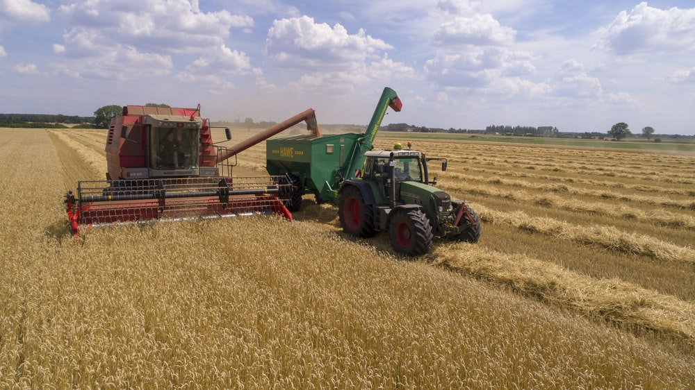 two green and red cultivators on brown field