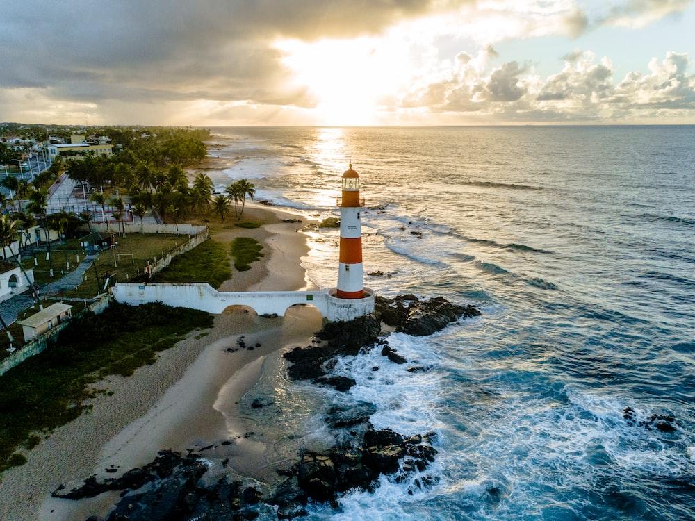 white and orange lighthouse beside sea