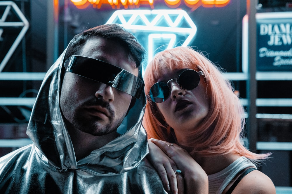 man and woman wearing sunglasses near neon signage