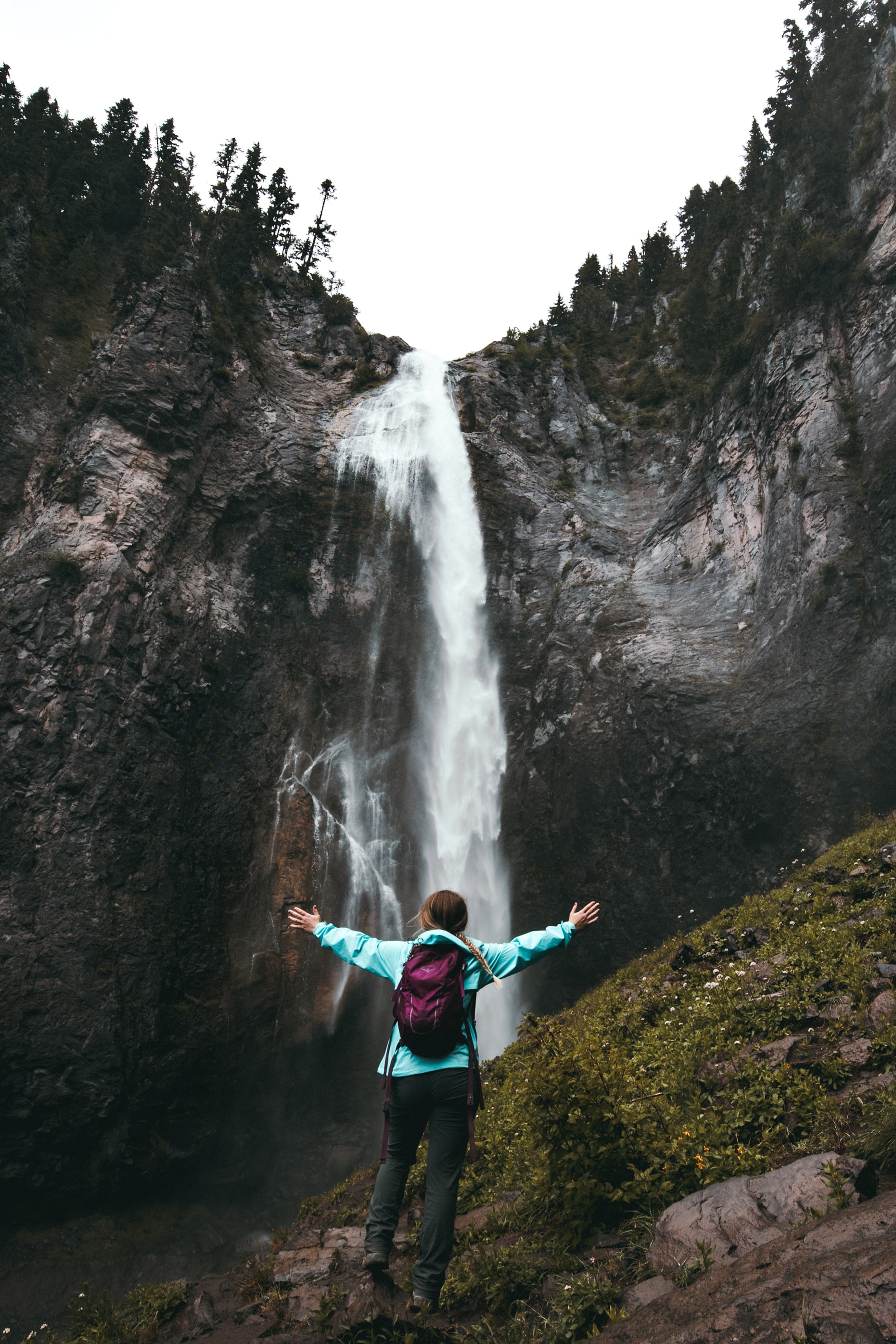 woman standing on hill facing waterfalls