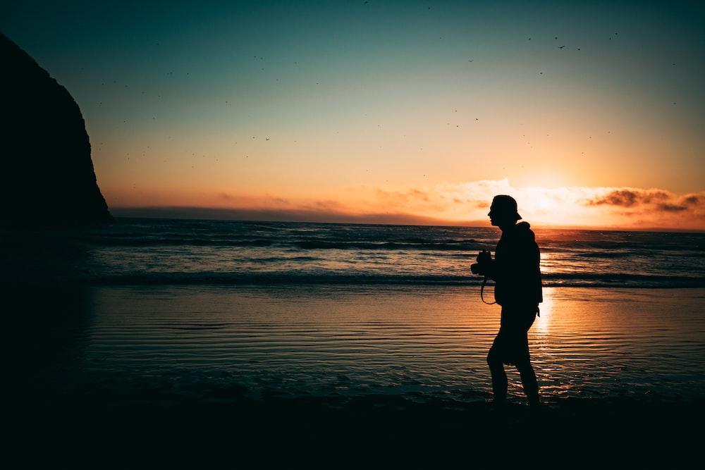 man walking on seashore at golden hour