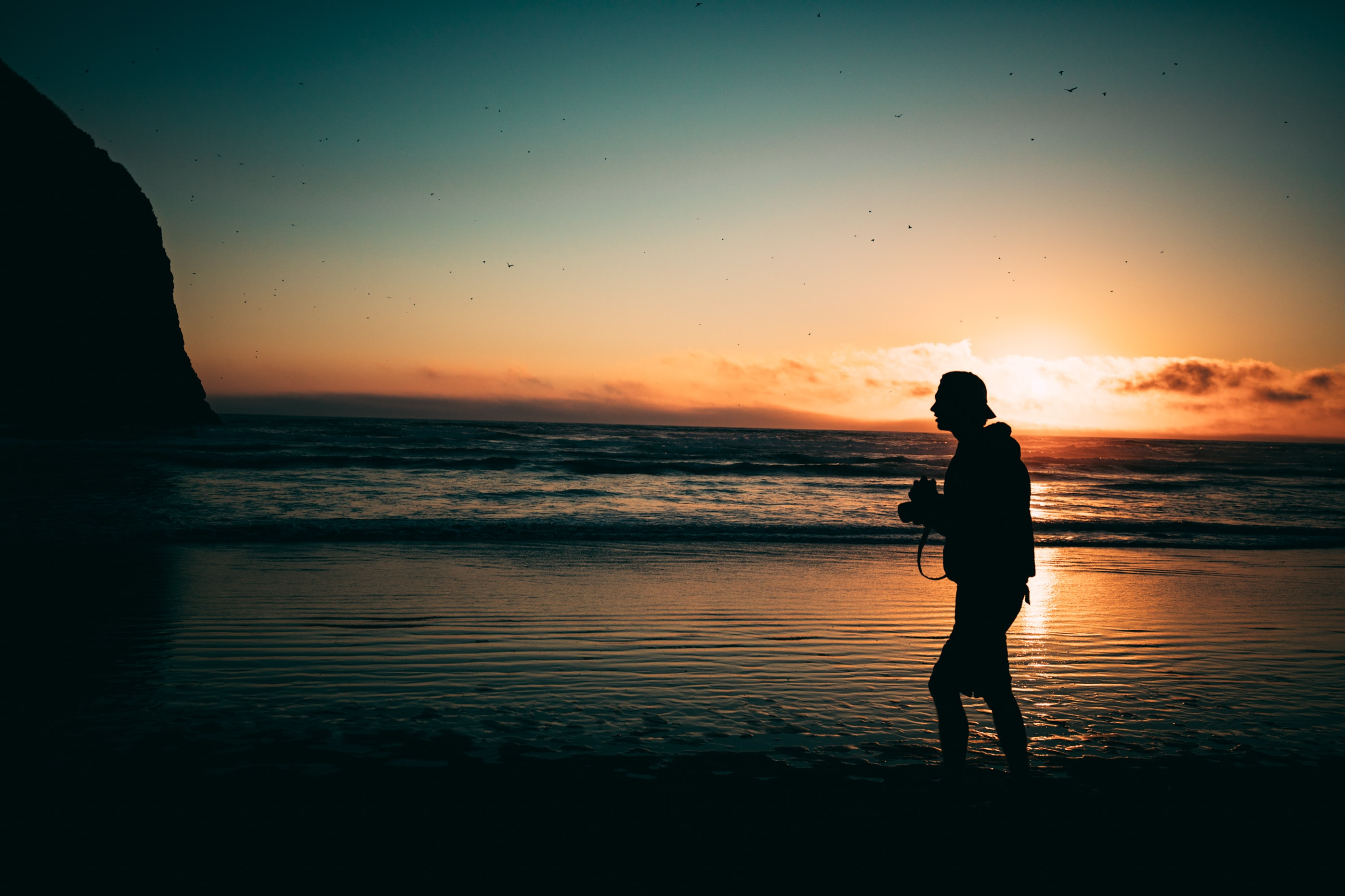 man walking on seashore at golden hour
