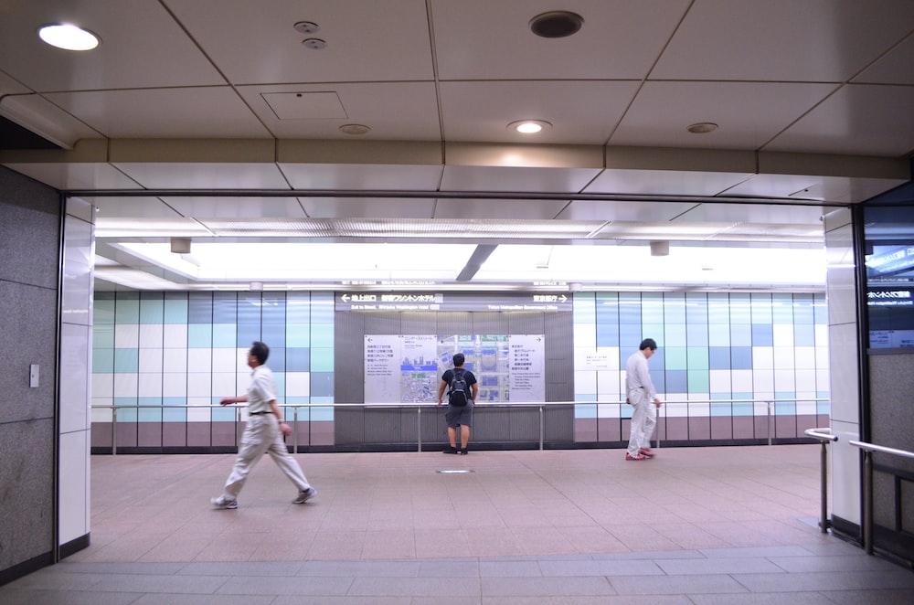 three person walking on train hallway